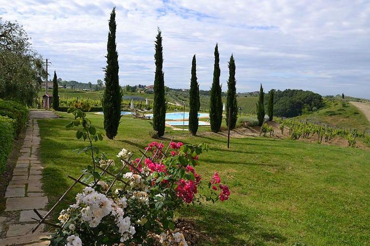 Un ampio giardino con fiori, alberi e piante circonda gli appartamenti