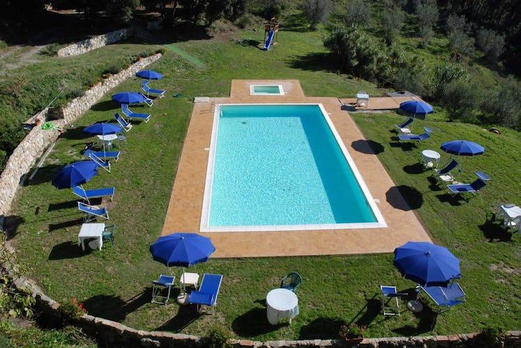 La piscina con l'angolo dedicato ai bambini, sdraio ed ombrelloni