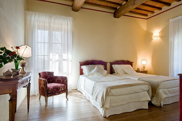 La camera Ciliegio, con pavimenti in parquet e soffitti con travi a vista