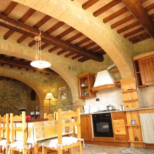 Archi in pietra e travi a vista accentuano il tipico stile toscano