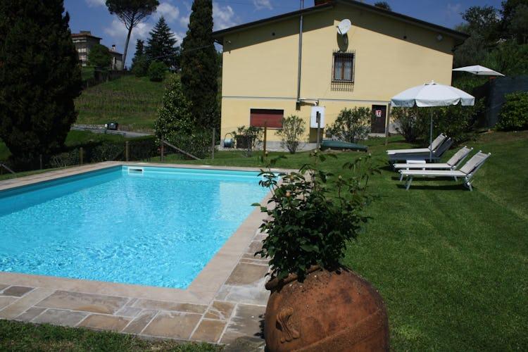Casa Vacanze i Cipressi: l'area della piscina con sdraio e ombrelloni