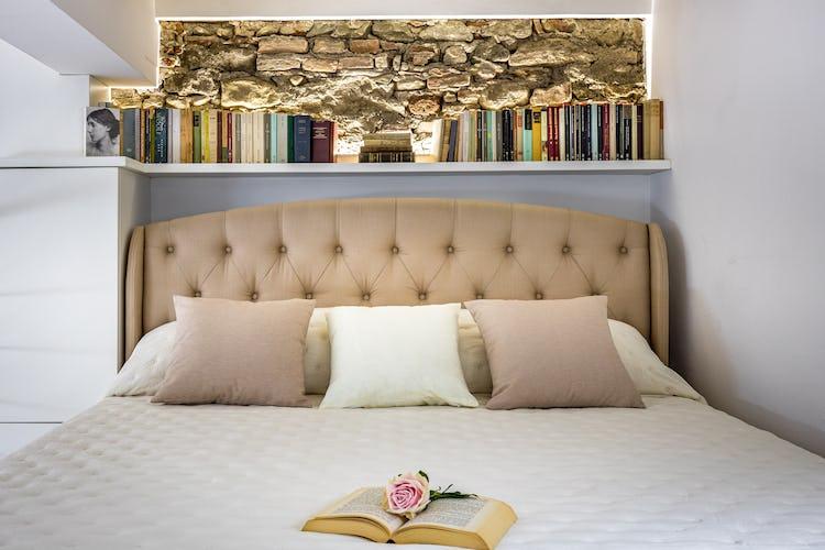 Il letto matrimoniale ubicato sul soppalco a vista e circondato dai libri da cui prende il nome l'appartamento