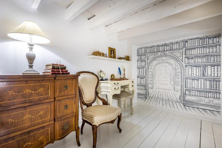 Sul soppalco, oltre al letto matrimoniale, è stata posizionata una scrivania per leggere uno dei tanti libri presenti