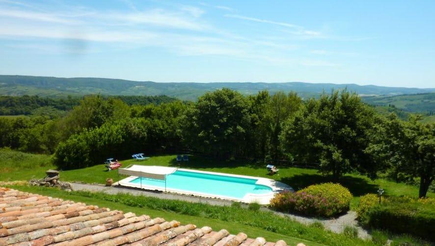 La piscina panoramica è circondata dall'ampio giardino con le sdraio