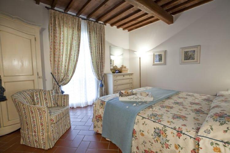 Soffitti con travi a vista e pavimenti in terracotta nelle camere