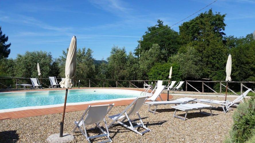 Ghiaia Holiday Villas & Homes: intorno alla piscina sono stati sistemati ombrelloni e sdraio per rilassarsi sotto il sole di Toscana