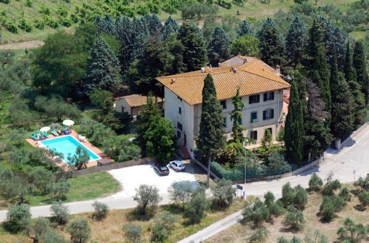 Villa I Leoni con l'ampio giardino e la piscina con sedie e sdraio